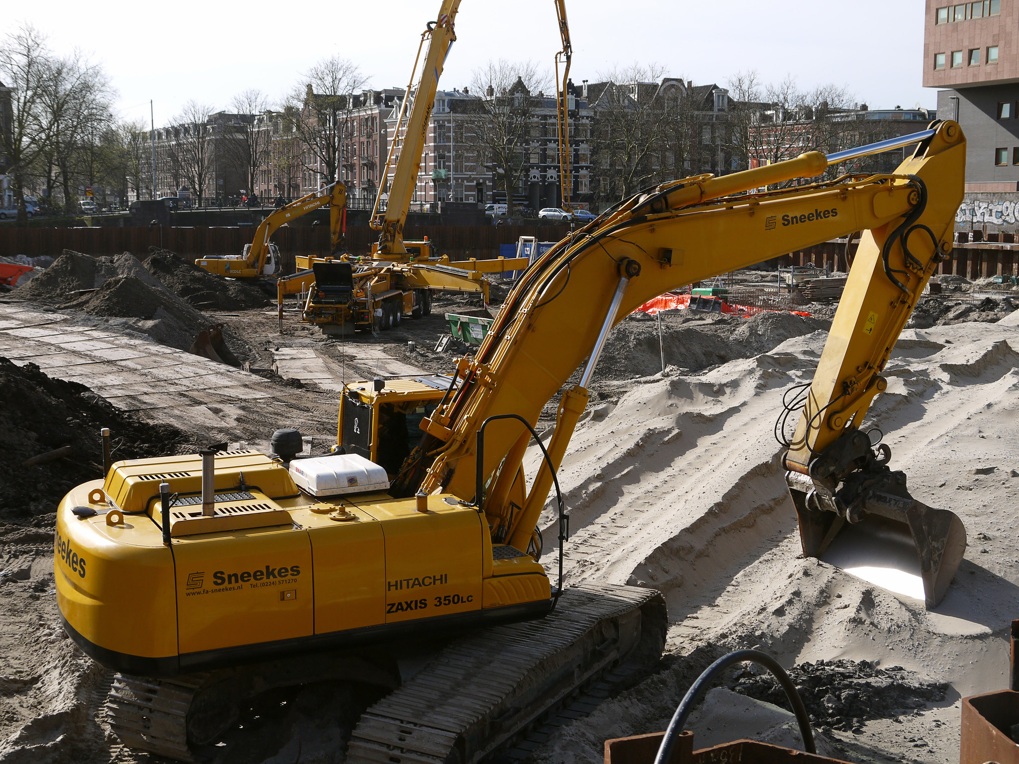 """2014.03 - Excavation site with cranes, diggers and building equipment, along the canal water; a geotagged free urban picture, in public domain / Commons CCO; city photography by Fons Heijnsbroek, The Netherlands"" by Amsterdam free photos & pictures of the Dutch city is marked with CC0 1.0"
